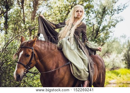 Elf woman in the forest with a horse