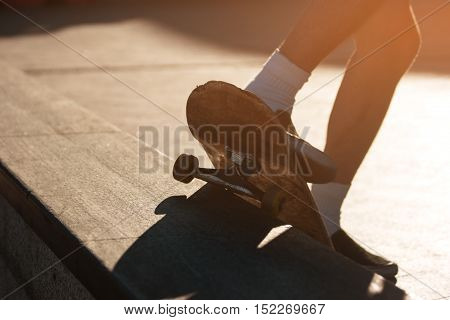 Feet and skateboard. Skater doing grind trick. Perfect coordination of movements. Skill of extreme sportsman.
