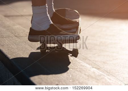 Feet on a skateboard. Skater performs a trick. Tutorial for perfect grind. Train your skills.