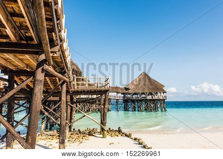 beautiful view of wooden pier with thatched roof in ocean and blue sky