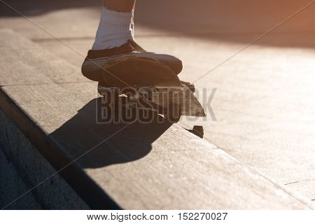 Feet doing trick on skateboard. Skater is grinding. Master the stunts. Hobby of youngsters.