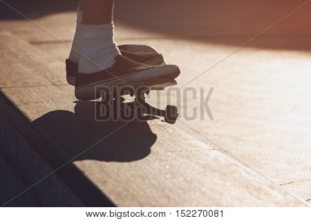 Feet standing on skateboard. Skater does a grind trick. Develop your skills. Sport of modern youth.