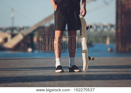 Person standing near skateboard. Skater wearing shorts. I fear nothing. Confidence and stubbornness.
