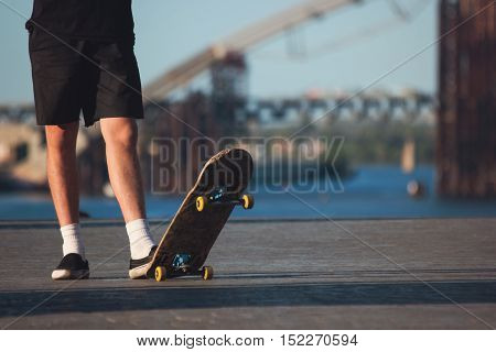 Guy with skateboard outdoor. Legs of skateboarder standing. Sport of young and fearless. For those who love risk.