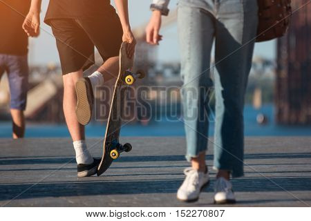 Person with skateboard. Legs of people outdoor. Sport of young generation. Stubbornness and enthusiasm.