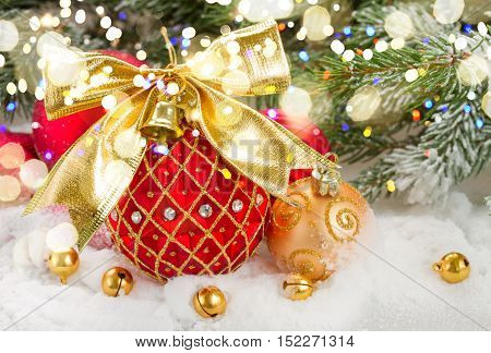 red christmas ball with golden bow in snow under fir tree with lights bokeh