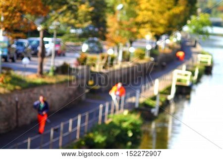Abstract high key blurred image of street workers on the river side in fall. Unrecognizable faces.