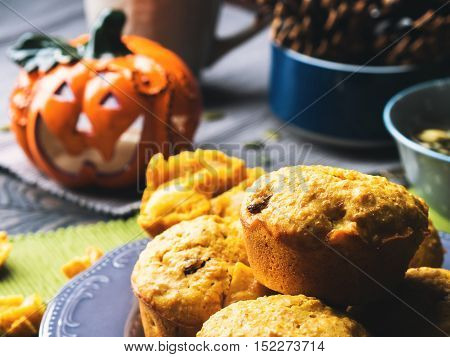 Pumpkin whole grain muffins with raisins and pumpkin seeds on dark background with a halloween decorative squash. Toned