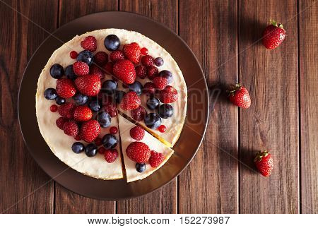 Top view. Delicious Homemade creamy mascarpone New York Cheesecake with berries on dark wooden table. Close up. Cream mousse cake. Rustic style.