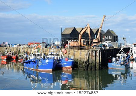 Whitstable United Kingdom -October 1 2016: Fishing Boats in Whitstable Harbour with warehouse in background