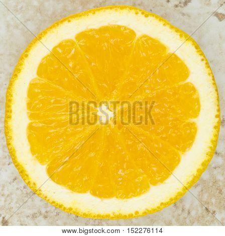 Slice of orange up close on a textured background