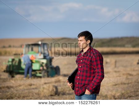 Farmer In Field With Tractor In Background