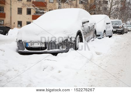 Stockholm, Sweden - December 20, 2012: Snow in parked cars on Furusundsgatan. A snow bank by a snowplow complicates driveway with the car.