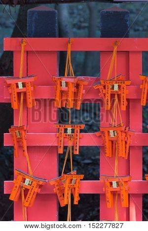 Kyoto Japan - September 17 2016: Closeup of nine wooden prayer boards in the shape of Torii at Fushimi Inari Taisha Shinto Shrine. Left by worshipers writing down their wishes and pleas for the spirits of the ancestors.