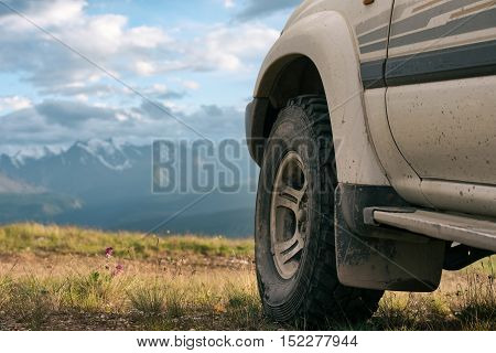 Offroad car concept with mountains. Wheel close-up