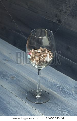 Medical Capsules And Tablets Inside Wine Glass
