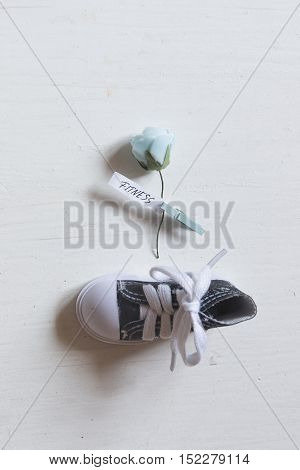 Fitness concept. Rose with text one shoe on a white table.