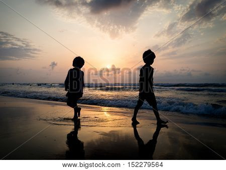Kids silhouettes having happy time on sea beach near sunset