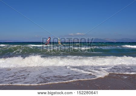 Beautiful view on the Aegean sea with two windsurfers from sandy beach in Artemis Greece