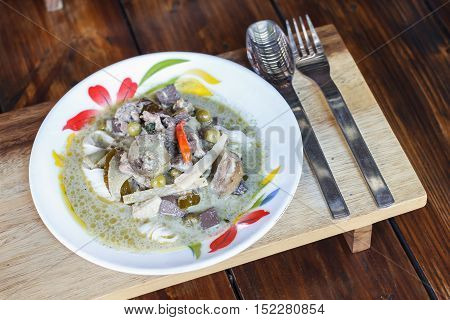 Green curry chicken with Thai rice noodles on wooden table. Thai Food.