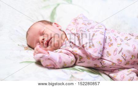 Little newborn baby sleeps in her crib