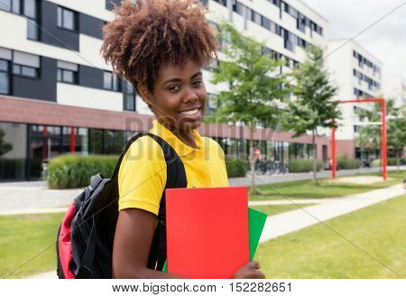 Laughing african american female student outdoor on campus of university in the summer