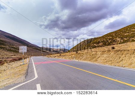Asphalt road High way Empty curved road clouds sky and mountains at China.