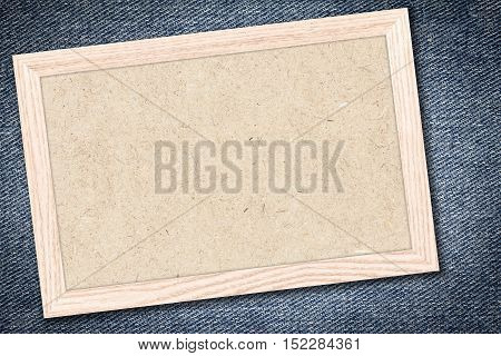Chipboard or Empty bulletin board with a wooden frame on denim jeans background with copy space for text or image.