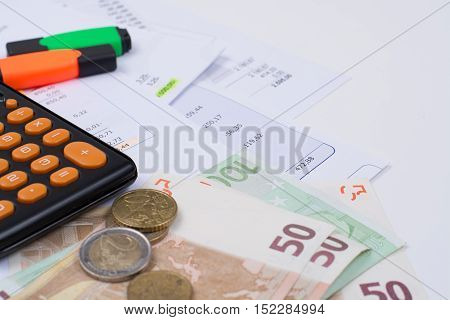 Utility or mortgage bills calculator and Euro banknote and coins - finance concept payments and problems