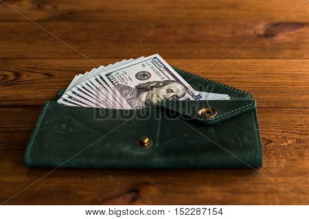 Accumulation. A lot of dollars in the green purse