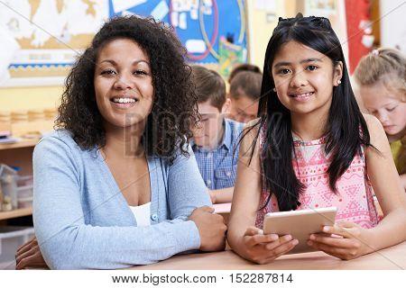 Teacher Helping Group Of Elementary School Children In Computer Class