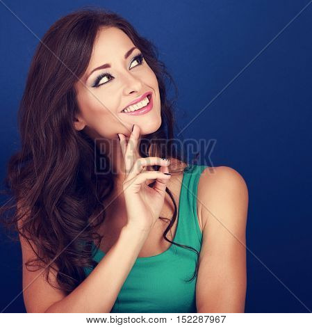 Thinking Success Beautiful Brunette Woman With Finger Under Face Looking Up On Blue Background. Clos