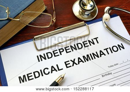 Independent Medical Examination (IME) form on a wooden table.