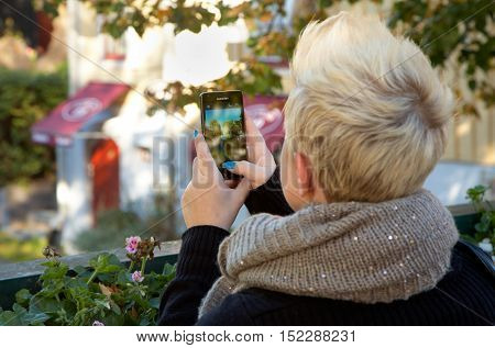 Trosa, Sweden - October 6, 2012: Young woman photographing Trosa River with a smartphone.