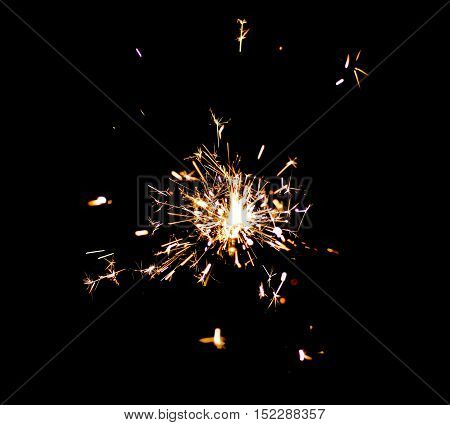 Single bright festive New Year Christmas sparkler on black background