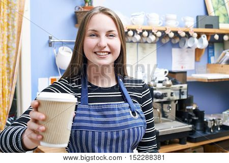 Waitress In Cafe Serving Customer With Takeaway Coffee
