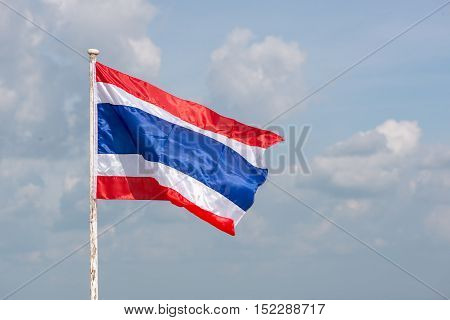 A lone Thai flag waving in the wind on a bright sunny day with clouds in the background.