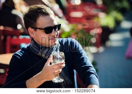 Young man sitting at outdoor bar table having a glass of white wine and looking to camera.