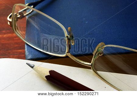 Pencil with notepad and glasses on wooden table.