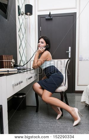 Attractive woman talking on land line indoors