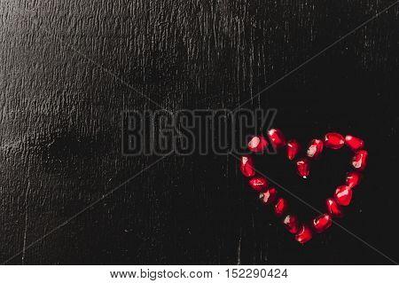 Delicious Pomegranate Fruit Heart Shape On Black Background