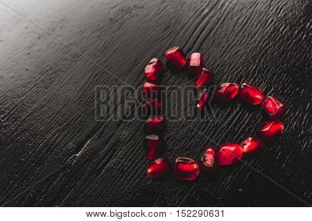 Delicious pomegranate red fruit on black background