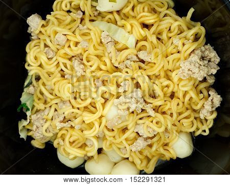 Yellow instant noodle in black bowl Closeup top view