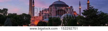 Hagia Sophia at sunset with motion blurred people walking by and illuminated fountain. Istanbul Turkey