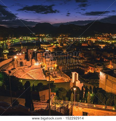Aerial view of port city Cartagena in Spain with famous roman amphitheater. Beautiful sunset over the mountains.