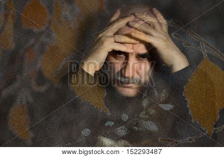 Multiple exposured portrait of sad mature man with arms enfolded head