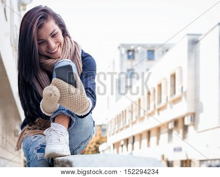 Pretty brunette female using her phone and laughting