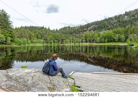 Alone young girl sitting and resting near by beautiful blue lake and clear big mountains. Original wallpaper from summer morning