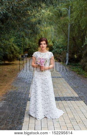 Bride in the park in the alley on a rainy day