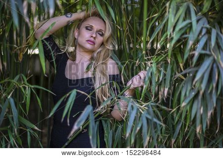 health, beautiful blonde with long black discharge between branches and trunks of vegetation